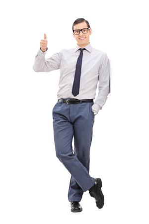 posing  agree: Full length portrait of a young elegant man giving a thumb up and looking at the camera isolated on white background Stock Photo