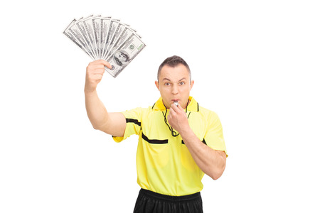 ref: Furious football referee blowing a whistle, holding a stack of money and looking at the camera isolated on white background Stock Photo