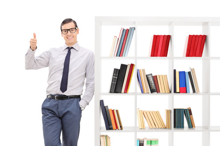 posing  agree: Young man giving a thumb up, leaning on a bookshelf and looking at the camera isolated on white background Stock Photo