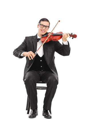 violin background: Cheerful young violinist playing an acoustic violin seated on a wooden chair isolated on white background Stock Photo
