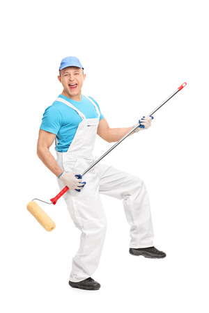 painter and decorator: Full length portrait of a delighted male house painter playing guitar on a paint roller isolated on white background Stock Photo