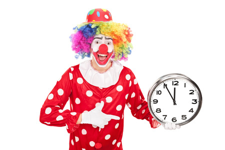 Young male clown holding a big wall clock in one hand and pointing towards the clock with the other isolated on white background Stock Photo
