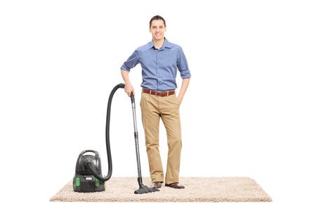 personal de limpieza: Hombre joven que presenta al lado de una aspiradora en una alfombra de color beige aislados sobre fondo blanco Foto de archivo