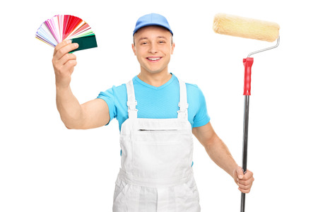jumpsuit: Young male painter in a white jumpsuit holding a paint roller and color guide isolated on white background Stock Photo