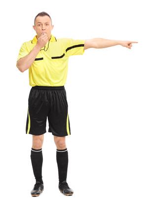 arbitros: Retrato de cuerpo entero de un árbitro de fútbol enojado soplando un silbato y señalando con la mano aisladas sobre fondo blanco Foto de archivo