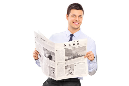 Handsome man holding a newspaper and leaning against a wall isolated on white background