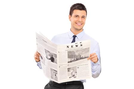 periodicos: Hombre hermoso que sostiene un periódico y apoyado contra una pared aislada sobre fondo blanco Foto de archivo