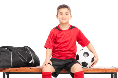 junior soccer: Junior soccer player sitting on a bench and holding a football isolated against white background Stock Photo