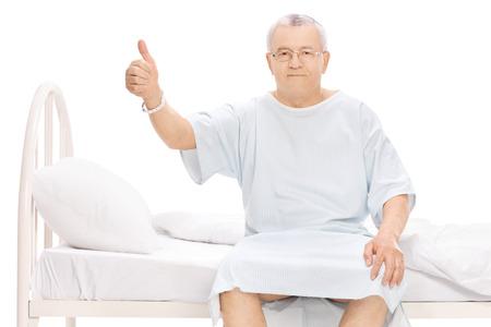 成熟した患者は病院のベッドの上に座って、親指をあきらめると白い背景で隔離のカメラを見て