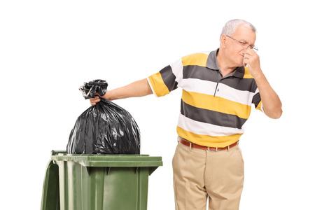 Senior weggooien van een stinkende zak vuilnis op een witte achtergrond Stockfoto
