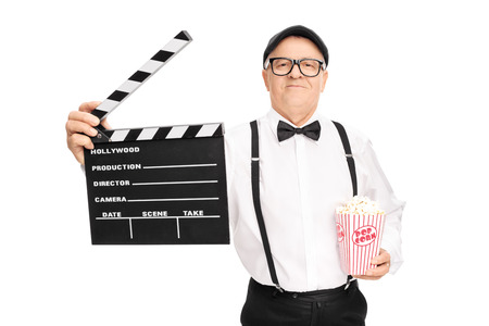 movie director: Mature movie director holding a clapperboard and a box of popcorn isolated on white background