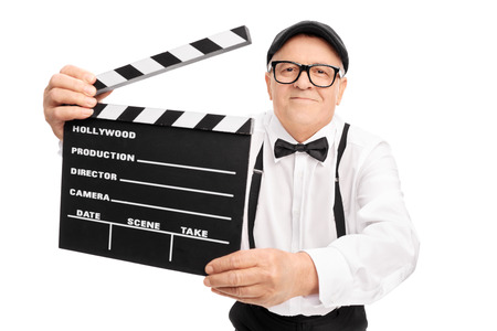 movie director: Senior movie director holding a movie clapper, smiling and looking at the camera isolated on white background Stock Photo