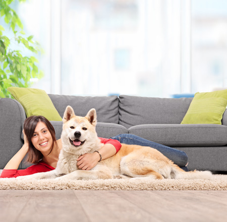 hug: Young girl lying on the floor with her pet dog and hugging the dog by a gray couch at home shot with tilt and shift lens