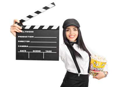 board of director: Young female movie director holding a movie clapper board and a box of popcorn isolated on white background
