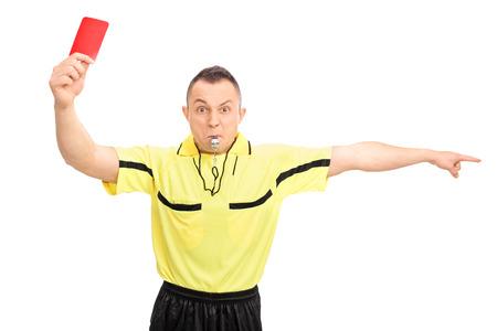 Boos voetbal scheidsrechter in een gele trui met een rode kaart en wijst met zijn hand op een witte achtergrond Stockfoto