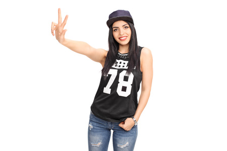 rnb: Beautiful young woman in a hip-hop outfit making a hand sign and looking at the camera isolated on white background