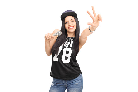 Young female hip-hop artist singing on a microphone and making a hand sign isolated on white background photo