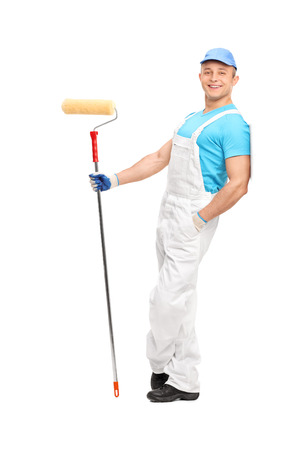 jumpsuit: Full length portrait of a relaxed young painter in a white jumpsuit holding a paint roller and leaning against a wall isolated on white background Stock Photo