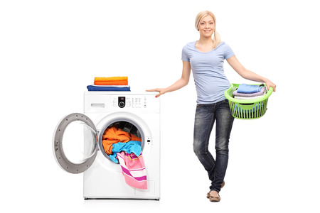 lavado: Retrato de cuerpo entero de una mujer joven sosteniendo un cesto de la ropa llena de ropa doblada y posando junto a una lavadora aisladas sobre fondo blanco Foto de archivo