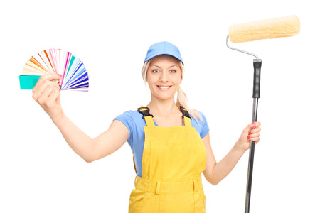 decorator: Blond female decorator holding a paint roller and a color palette guide isolated on white background