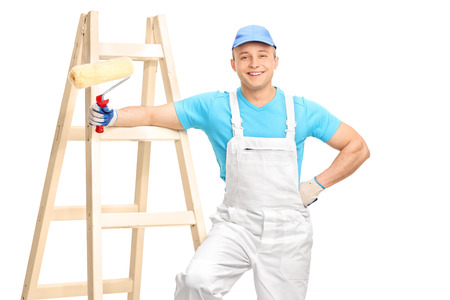 decorator: Cheerful male decorator in a white jumpsuit and a blue shirt holding a paint roller and leaning on a wooden ladder isolated on white background