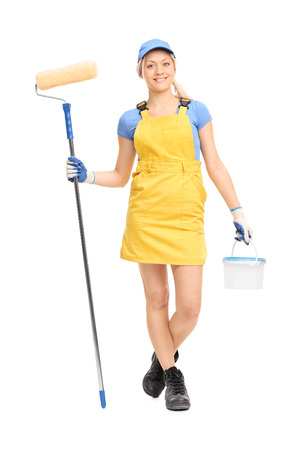 overall: Full length portrait of a young female house painter in a yellow overall walking with a paint roller and a color bucket isolated on white background