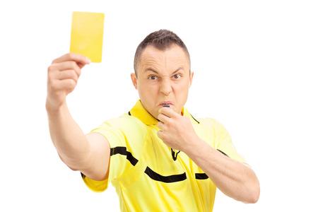 猛烈なサッカーの審判は黄色のカードを示すと白い背景で隔離の笛を吹く