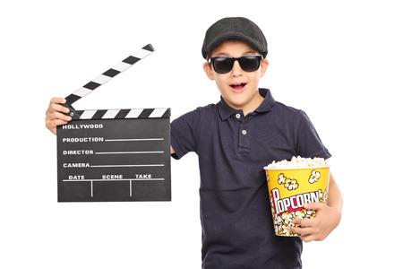 palomitas: Niño con una boina y gafas de sol que llevan a cabo una caja de palomitas de maíz y una claqueta de cine aislado en fondo blanco