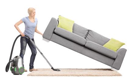 casalinga: Forte casalinga muovere un divano con una mano e passare l'aspirapolvere sotto di esso isolato su sfondo bianco