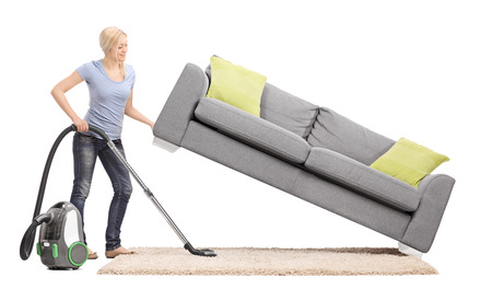 white carpet: Strong housewife lifting a sofa with one hand and vacuuming underneath it isolated on white background