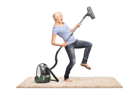 personal de limpieza: Mujer emocionada joven que limpia con un aspirador y fingiendo estar tocando la guitarra en el tubo aislado en fondo blanco