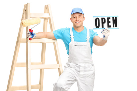 jumpsuit: Young male house painter in a white jumpsuit and blue shirt holding a paint roller and an open sign isolated on white background Stock Photo