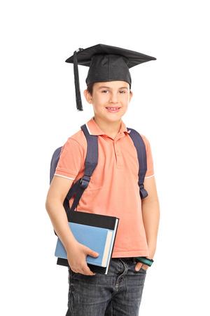 graduacion niños: Colegial con un sombrero de graduación que lleva una mochila y la celebración de un par de libros aislados sobre fondo blanco