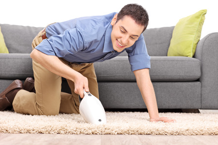 carpet clean: Young joyful man vacuuming a carpet with a handheld vacuum cleaner isolated on white background