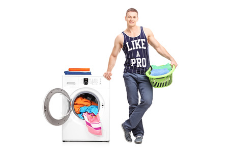 man machine: Full length portrait of a young man holding a laundry basket next to a washing machine isolated on white background