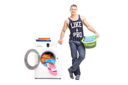 lavando ropa: Retrato de cuerpo entero de un hombre joven sosteniendo un cesto de la ropa junto a una lavadora aisladas sobre fondo blanco