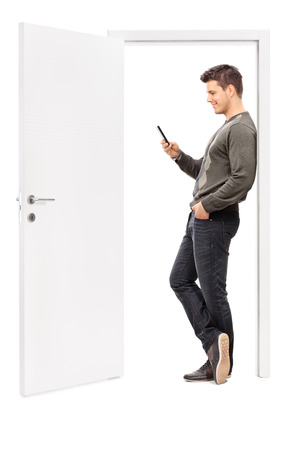 surfing the net: Full length portrait of a young man surfing the net on his cell phone and leaning on the frame of an opened door isolated on white background Stock Photo