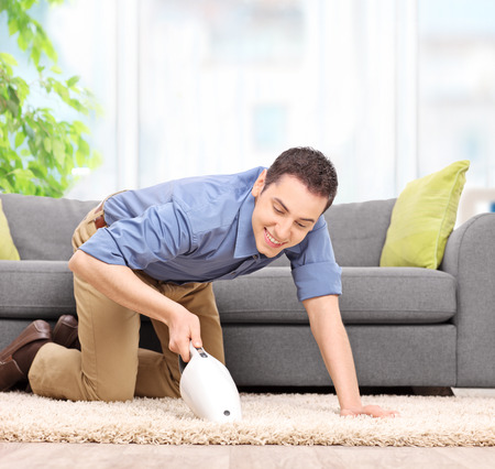 carpet clean: Young man vacuuming a carpet with a handheld vacuum cleaner and smiling at home shot with tilt and shift lens