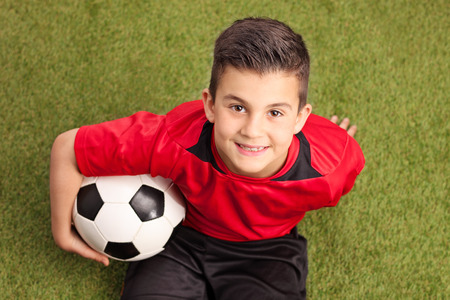 High angle shot of a junior football player in a red jersey sitting on grass holding a ball and smiling Stock Photo