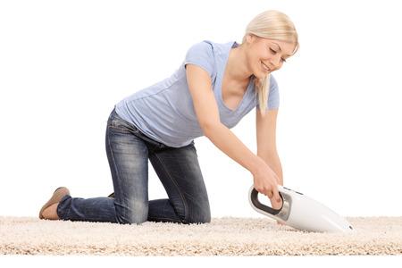 白い背景に分離されたハンドヘルド掃除機でカーペットをクリーニング若い金髪女性