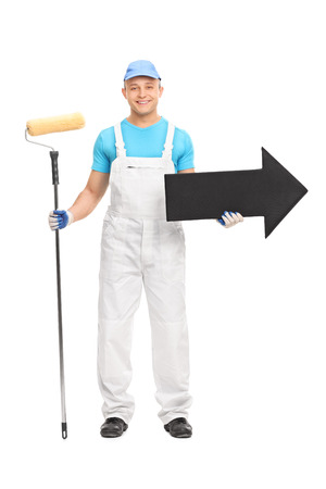 decorator: Full length portrait of a young male decorator in a white uniform holding a paint roller and a big black arrow pointing right isolated on white background