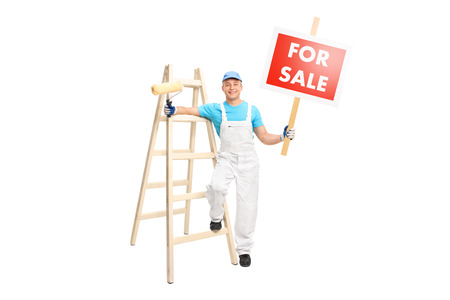 placard: Full length portrait of a young male painter posing next to a wooden ladder and holding a paint roller in one hand and a for sale sign in the other isolated on white background Stock Photo