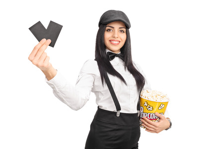 movie director: Cheerful female movie director holding a box of popcorn and two tickets isolated on white background