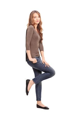 length: Full length profile shot of a casual young woman leaning against a wall and posing isolated on white background