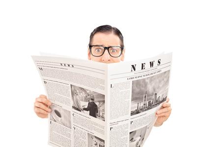 periodicos: Hombre aterrorizado celebración de un periódico y mirando a la cámara aislada en el fondo blanco