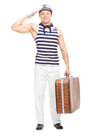 saluting: Full length portrait of a young male sailor saluting towards the camera and holding a briefcase isolated on white background Stock Photo