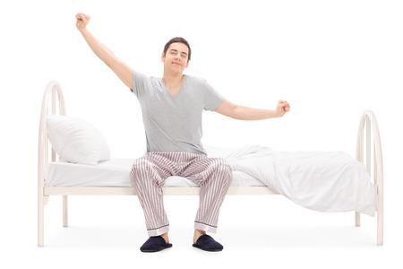 陽気な男の眠りから目を覚ます、彼の白い背景で隔離のベッドに座ってストレッチ