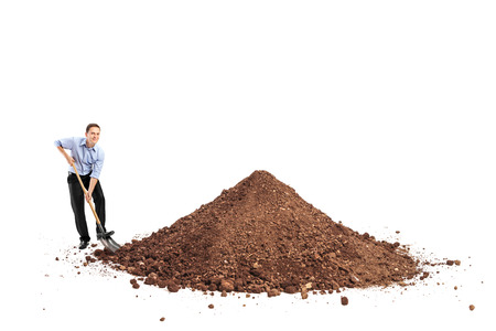 Cheerful young man shoveling a big pile of dirt and looking at the camera isolated on white background photo