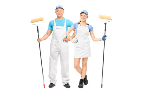 studio happy overall: Male and a female house painters holding paint rollers and posing in white uniforms isolated on white background Stock Photo