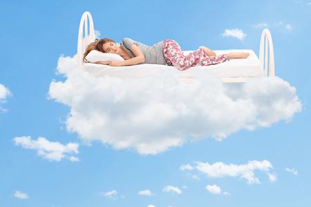 sono: Relaxado jovem mulher que dorme em uma cama confortável nas nuvens Imagens